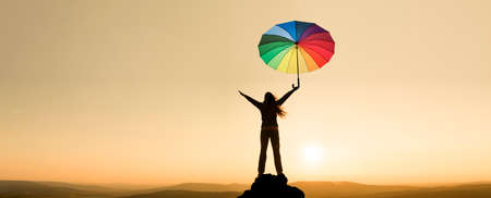 Woman with an umbrella on a mountain top