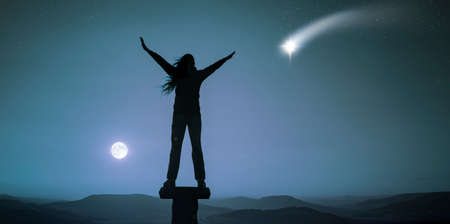Woman with arms outstretched on a full moon night