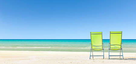 Sun chairs on beach with blue sea