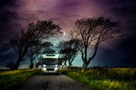 Motorhome on a narrow country road with trees
