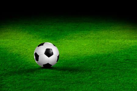 Football on soccer field in the spotlight