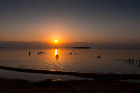 The Dead Sea is a salt lake in Israel. Its shores are the lowest point on the surface of the Earth on dry land. The lake is very salty (around 30% salt), causing people to float on its waters. photo