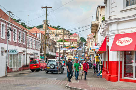 afro caribbean ethnicity: St. Georges, Grenada - December 3, 2011: Scene of daily life in the capital of Grenada, with people walking on the sidewalks and traffic in the streets. The center of the city is crossed by steep, narrow streets full of shops and people.