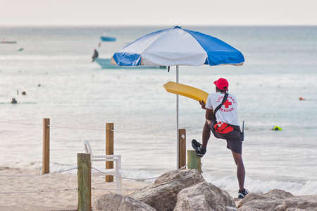 incidental people: Eleuthera, Bahamas - December 7, 2011: A red cross lifeguard is patrolling the tropical beach of the Princess Cays, Eleuthera Islands in the Bahamas on December 7, 2011.