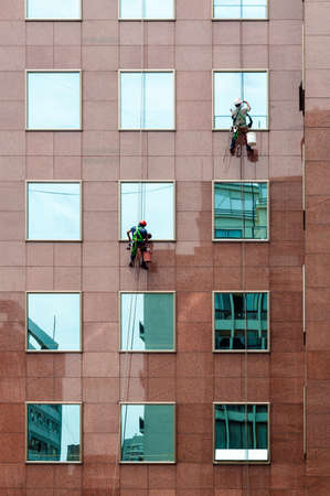 rappelling: Santiago, Chile - December 01, 2012: Two window cleaners at work and offices building at December 01, 2012.