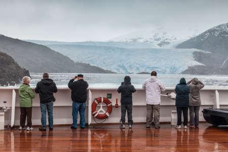 sarmiento: Amilia Glacier, South Patagonia, Chile, - December 8, 2012: Passengers on board the cruise ship Veendam viewing beautiful glacier. Taken at the Sarmiento Channel, Chile on a overcast rainy day. Amalia Glacier, also known as Skua Glacier, is a tidewater gl