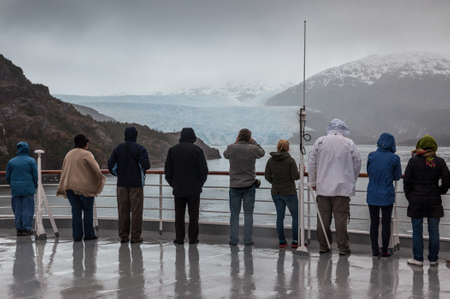 sarmiento: Amilia Glacier, South Patagonia, Chile - December 8, 2012: Passengers on board the cruise ship Veendam viewing beautiful glacier. Taken at the Sarmiento Channel, Chile on a overcast rainy day. Amalia Glacier, also known as Skua Glacier, is a tidewater gla
