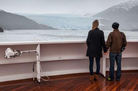 sarmiento: Amilia Glacier, South Patagonia, Chile - December 8, 2012: Couple on board the cruise ship Veendam viewing beautiful glacier. Taken at the Sarmiento Channel, Chile on a overcast rainy day. Amalia Glacier, also known as Skua Glacier, is a tidewater glacier Editorial