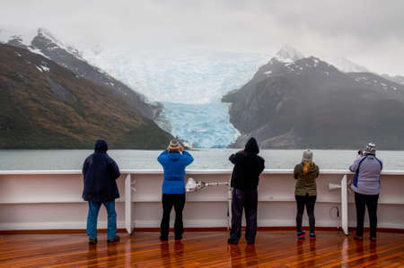 discovery channel: Glacier Alley, Beagle Channel, Chile - December 10, 2012: Passengers on board the cruise ship Veendam viewing beautiful Italia Glacier on Glacier Alley. Taken on a overcast rainy day. Glacier alley is also of historical importance as it was described in d
