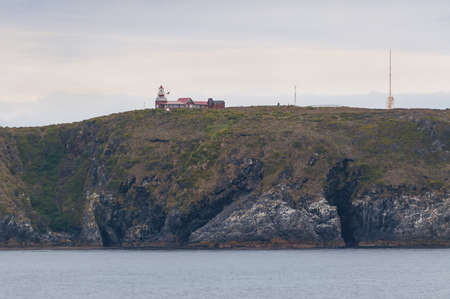 administered: Cape Horn Lighthouse. The unmanned light station is the southernmost point of Cape Horn and is administered by the Chilean Navy. Cape Horn is where the Atlantic and Pacific Oceans meet and lies on the north edge of the Drake Passage. Stock Photo
