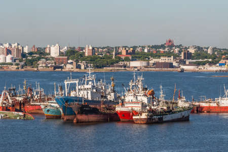 ruination: Montevideo, Uruguay - December 15, 2012: The abandoned old rusty ship in the Port of Montevideo, Uruguay at December 15, 2012. Montevideo in the background.
