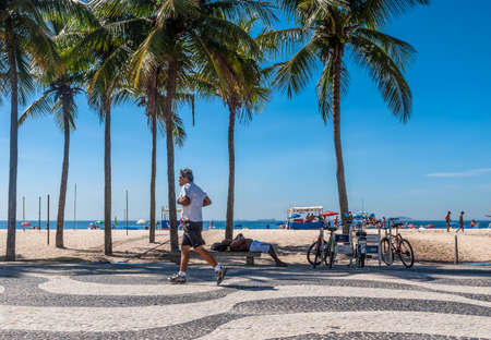 predicted: Rio de Janeiro, Brazil - December 21, 2012: People run around and relax on Copacabana sidewalk at Rio de Janeiro. New Age writers cite Mayan and Aztec calendars which predicted the end of the age on Dec 21, 2012. Editorial