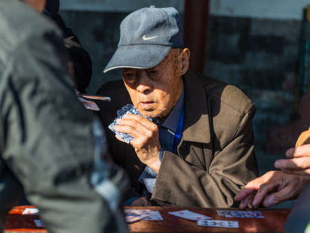 only senior men: Beijing, China - October 15, 2013: Portrait of a Elderly Chinese men enjoying a game of cards with friends in the surroundings of the Temple of Heaven in Beijing, China.