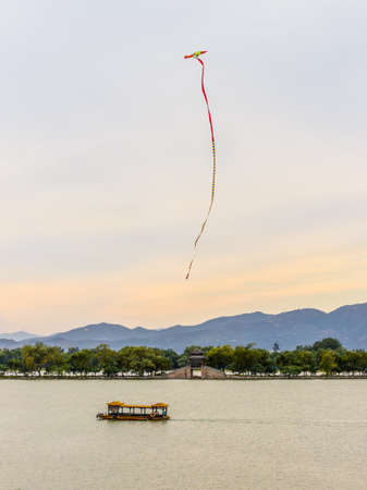 readily: Beijing, China - October 14, 2013: Kite flying in the sky over the Kunming lake at the Summer Palace. Kiting is a very old Chinese tradition. 2,800 Years ago kites were already used in China, where materials ideal for kite building were readily available: Editorial