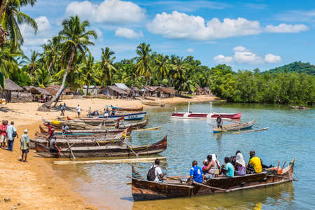 woo: Ambatozavavy, Nosy Be, Madagascar - December 19, 2015: Boaters on their traditional wood pirogue with outrigger waiting for passengers in the Ambatozavavy village on the island of Nosy Be, Madagascar. Traditional fishing village on Nosy Be island with woo Editorial