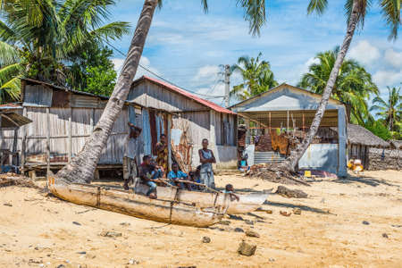 outrigger: Ambatozavavy, Nosy Be, Madagascar - December 19, 2015: Locals relax in the shade  near traditional wood pirogue with outrigger in the village of Ambatozavavy on the island of Nosy Be, Madagascar. Traditional fishing village on Nosy Be island with wooden d Editorial
