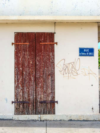 gaulle: A wooden old door and plate with name of the street, rue du General de Gaulle, in Saint Paul on the island of La Reunion (France) in the Indian ocean. Stock Photo