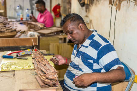 floreal: Floreal, Mauritius - December 26, 2015: Man working on wood sailing ship model at the Le Port Ship Models factory in Floreal, Mauritius.
