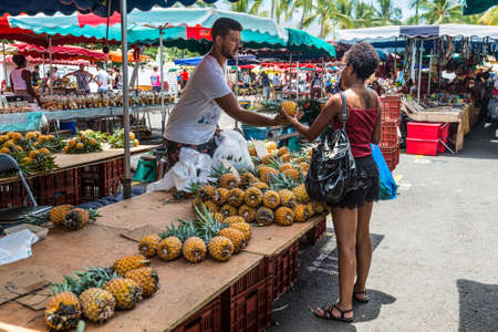 being the case: Saint-Paul, Reunion Island, France - December 24, 2015: Vendor fresh fruit pineapple on a local market in Saint Paul on the island of La Reunion (France) in the Indian ocean. Editorial
