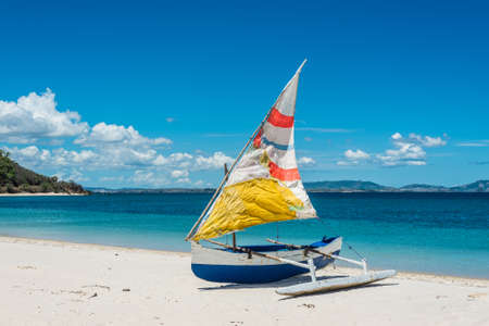 resourceful: Malagasy outrigger pirogue with colorful makeshift sails on the white beach