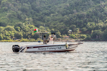 poppers: Hell-Ville, Madagascar - December 19, 2015: The speedboat of the Aviavy Fishing Club floats along the Hell-Ville harbour, Nosy Be Island, Madagascar. The waters around Nosy Be are ideal for practicing almost all fishing techniques: throwing poppers, troll
