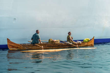 outrigger: Hell-Ville, Madagascar - December 19, 2015: Malagasy vendors from their outrigger canoe offer crabs, fish and tropical fruits to ship passengers at Hell-Ville, Nosy Be Island, Madagascar.