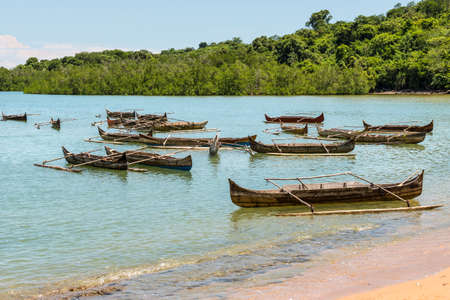 dugout: Traditional wooden dugout rowing outrigger canoes on Nosy Be island