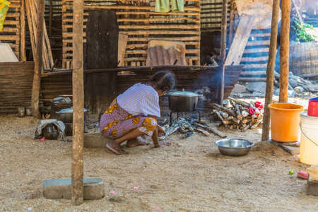 nosy: Ampasipohy, Nosy Be, Madagascar - December 19, 2015: An outdoor kithchen with and old woman cooking food in the rural village of the Ampasipohy, Nosy Be Island, Madagascar. Editorial