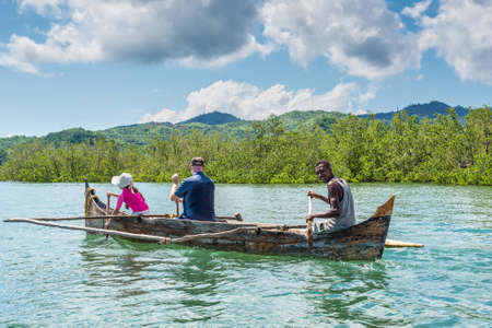 outrigger: Ambatozavavy, Nosy Be, Madagascar - December 19, 2015: Boatman, a man with a girl rowing oars by outrigger canoe near the Ambatozavavy village in Nosy Be island, north of Madagascar.