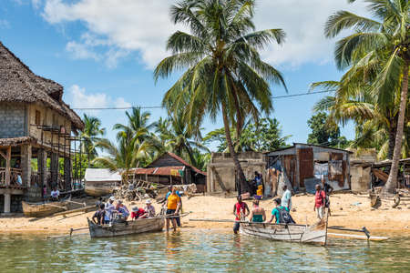 dugout: Ambatozavavy, Nosy Be, Madagascar - December 19, 2015: Tourists take places on their traditional wood pirogue with outrigger in the Ambatozavavy village on the island of Nosy Be, Madagascar. Traditional fishing village on Nosy Be island with wooden dugout