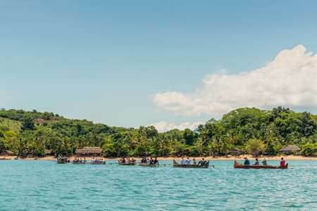 outrigger: Ampasipohy, Nosy Be, Madagascar - December 19, 2015: Caravan Malagasy traditional outrigger canoes with tourists arrived in Lokobe Strict Reserve in the village of the Ampasipohy, Nosy Be Island, Madagascar.
