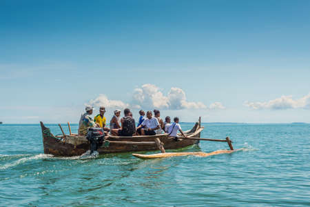 outrigger: Ambatozavavy, Nosy Be, Madagascar - December 19, 2015: Tourists with a guide crossing the inlets by outrigger canoe near the Ambatozavavy village in Nosy Be island, north of Madagascar.