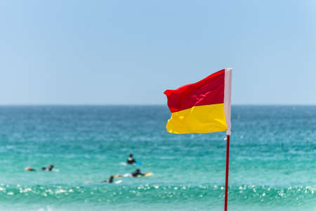 sky is the limit: Red and yellow flag marking the limit of the safe swimming area on a beach under a blue summer sky Stock Photo