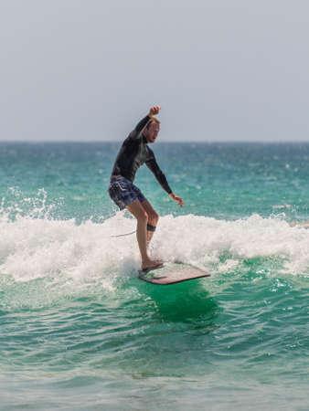 actividades recreativas: Manly, Australia - 9 de noviembre 2014: El hombre monta su tabla de surf hacia la orilla. Siete millas del centro de Sydney, Manly Beach ofrece una amplia gama de actividades deportivas y recreativas. Editorial