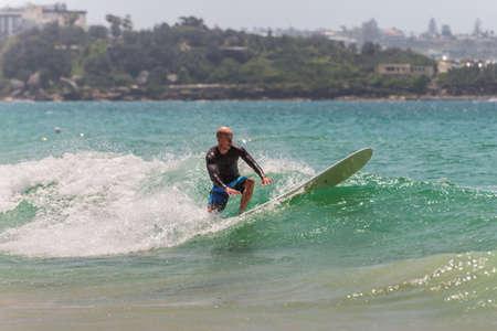 actividades recreativas: Manly, Australia - 9 de noviembre 2014: Un hombre navegar por una ola en la playa de Manly, trata de mantener el equilibrio. Siete millas del centro de Sydney, Manly Beach ofrece una amplia gama de actividades deportivas y recreativas.
