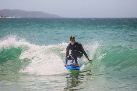 actividades recreativas: Manly, Australia - November 9, 2014: A man rides his surfboard towards the shore. Seven miles from the heart of Sydney, famous Manly beach offers a wide range of sports and recreational activities.