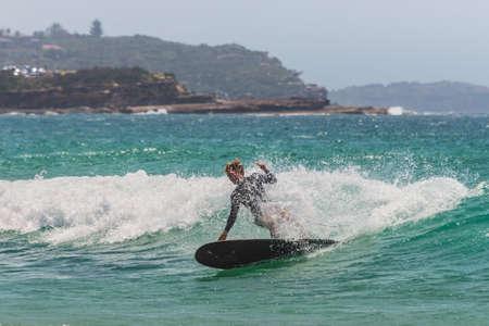 actividades recreativas: Manly, Australia - 9 de noviembre 2014: Un surfista australiano sobre la ola. Siete millas del centro de Sydney, Manly Beach ofrece una amplia gama de actividades deportivas y recreativas.