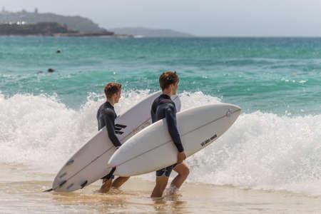 actividades recreativas: Manly, Australia - 9 de noviembre 2014: Dos surfistas australianos caminando hacia el mar y a surfear. Siete millas del centro de Sydney, Manly Beach ofrece una amplia gama de actividades deportivas y recreativas.
