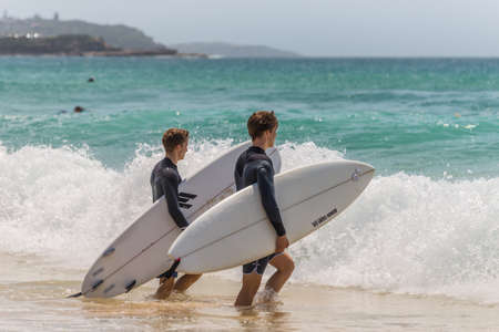 manly: Manly, Australia - November 9, 2014:  Two Australian surfers walking towards the sea and going surfing. Seven miles from the heart of Sydney, famous Manly beach offers a wide range of sports and recreational activities.
