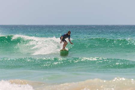 actividades recreativas: Manly, Australia - 9 de noviembre 2014: Un hombre monta su tabla de surf hacia la orilla. Siete millas del centro de Sydney, Manly Beach ofrece una amplia gama de actividades deportivas y recreativas.