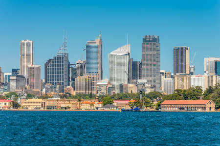 megapolis: Sydney, Australia - November 9, 2014: Australian Sydney landmark - city CBD high rises and towers forming megapolis cityscape summer day from harbour, Sydney, New South Wales, Australia. The Garden Island dockyard in the foreground.