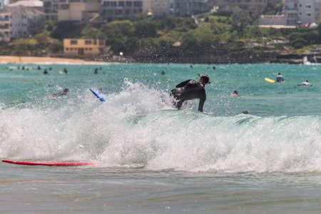 actividades recreativas: Joven surfista en la ola contra muchos otros surfistas. Siete millas del centro de Sydney, Manly Beach ofrece una amplia gama de actividades deportivas y recreativas.