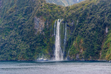 mariner: The Milford Mariner Ship near high waterfall at Milford Sound Fjord, New Zealand. This fiord is considered as one of the most scenic places in the world.