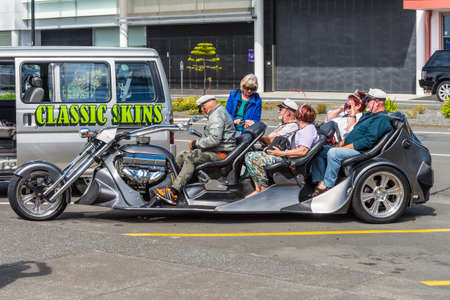 seater: Napier, New Zealand - November 19, 2014: People on a Five seater Trikey motorcycle seen in Napier New Zealand.