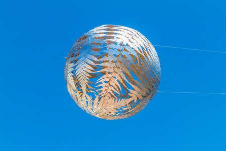 filagree: Wellington, New Zealand - November 18, 2014: Silver fern-patterned filagree suspended globe, Civic Centre, Wellington, New Zealand.