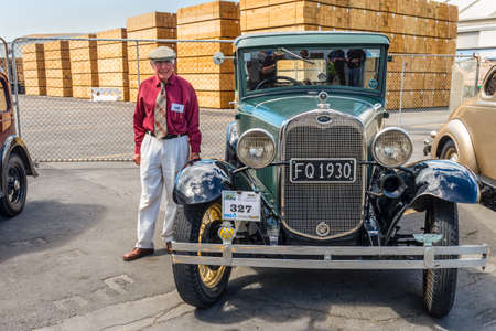 motorcars: Napier, New Zealand - November 19, 2014: Classic vintage 1930 Ford green saloon motor car and driver dressed in 1930s attire would chauffeur paying passengers around the quaint Art Deco seaside town of Napier on the North Island of New Zealand. Editorial