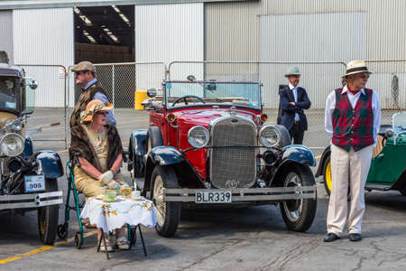 motorcars: Napier, New Zealand - November 19, 2014: Drivers and dame dressed in 1930s attire would chauffeur paying passengers around the quaint Art Deco seaside town of Napier on the North Island of New Zealand. Vintage cars are iconic sight of Napier street.