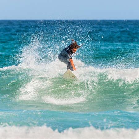 actividades recreativas: Sydney, Australia - 26 de noviembre 2014: Un hombre monta su tabla de surf hacia la orilla. Famosa playa de Bondi ofrece una amplia gama de actividades deportivas y recreativas.