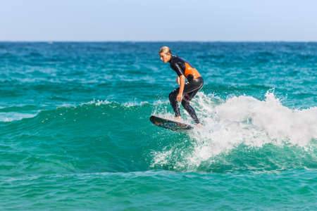 actividades recreativas: Sydney, Australia - November 26, 2014: A man rides his surfboard towards the shore. Famous Bondi Beach offers a wide range of sports and recreational activities. Editorial