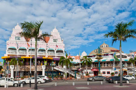 Oranjestad, Aruba - December 1, 2011: On Main Street, Oranjestad, stands a colorful mall containing shops and restaurants. Tourists can be seen entering the mall. Editorial